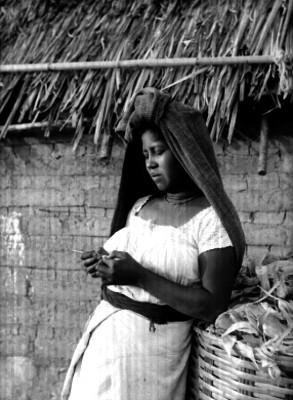 Indígena teje a gancho recargada en un cesto, retrato