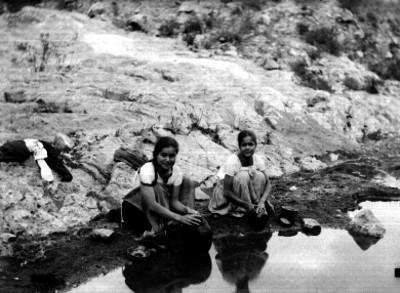 Mujeres lavan trastes en un río