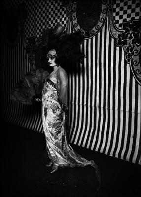 Actiz posa de pie con vestido largo satinado y un abanico de plumas, retrato