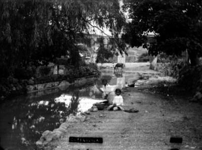"""Mujer lava ropa a la orilla de un río en """"Cuernavaca"""""""