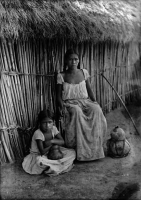 Mujer y niña sentadas afuera de una choza en Xochicalco, retrato