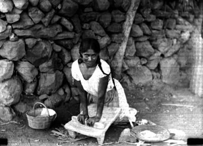 Mujer muele con metate en el suelo, retrato