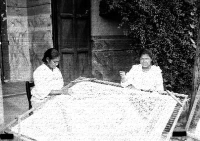 Mujeres deshilan mantel en un patio