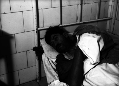 Hombre herido acostado en una cama de hospital
