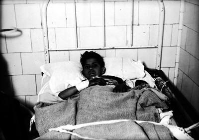 Niño herido acostado en una cama de hospital