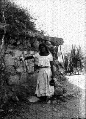 Mujer con jarro recargada en muro de piedra, retrato