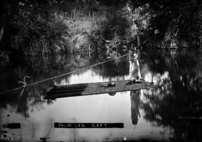Niña navega por un río en balsa hecha con troncos