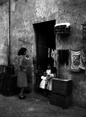 Mujer a la puerta de una casa con niños