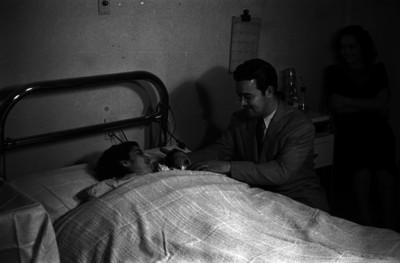 Padre y madre observan a su hijo recién nacido, interior de habitación de un hospital