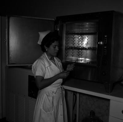 Enfermera sujeta una jeringa mientras esta junto a un congelador