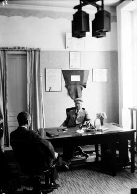 Francisco E. Elmer, médico, conversa con paciente en un consultorio