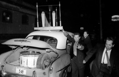 Hombres bajando instrumentos musicales de un automóvil