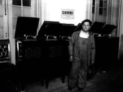Hombre junto a fonógrafos, en una tienda de aparatos radiofónicos