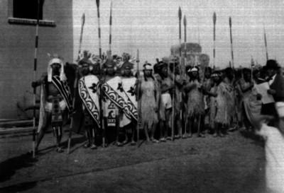 Personas con trajes folclóricos prehispánicos en una calle, retrato de grupo