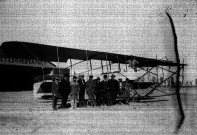 Alberto Braniff y otros hombres junto al Biplano Farman en un hangar de los llanos de Balbuena