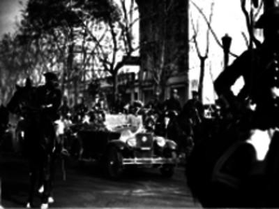 Charles Lindbergh, Dwight Morrow y otras personas en un automóvil escoltado por militares por una calle de la Cd. de México