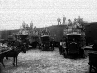 Hombres cargan camiones con mercancía bajada del ferrocarril