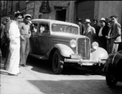 Hombres observado un automóvil en la calle