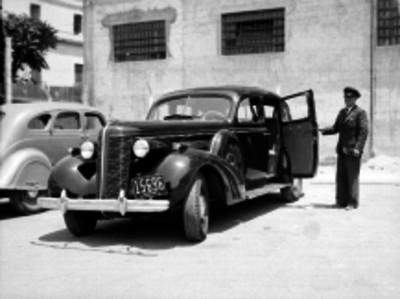 Chofer abriendo la puerta de un automóvil en un estacionamiento