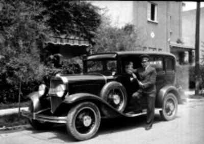 Chofer junto a un auto estacionado en patios de una casa, retrato