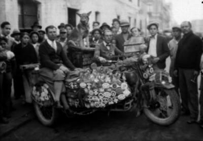 Hombres sobre triciclos motorizados en una calle, rodeados de gente