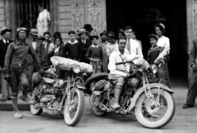 Hombres con motocicletas en una calle, retrato de grupo
