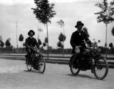 Hombres en motocicleta pasean por una calle