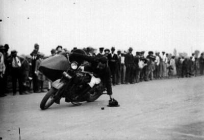 Acróbata en motocicleta recogiendo un sombrero del piso