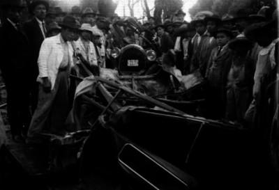 Gente observando los restos de automóviles