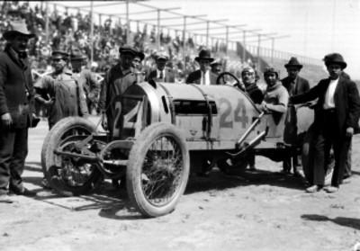 Pilotos a bordo de su auto acompañado por varios hombres en el autódromo de Chapultepec