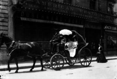 Mujeres abordo de un carruaje pasan frente a la American Photo Supply
