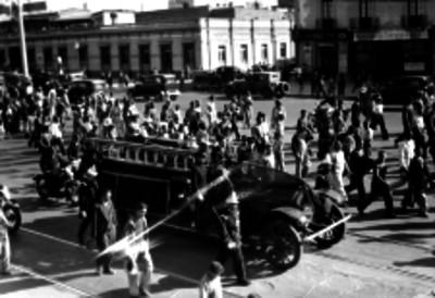 Carro de bomberos transportando un féretro por una calle
