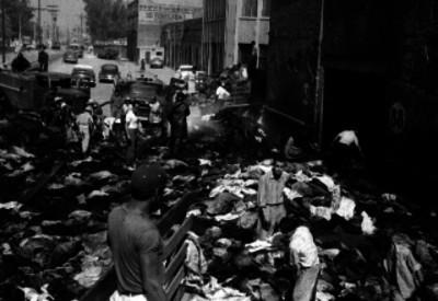 Bomberos y hombres entre los escombros de edificio incendiado