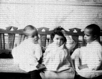Niños sentados sobre una banca, retrato de grupo