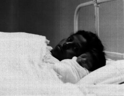 Mujer y bebé recostados sobre una cama