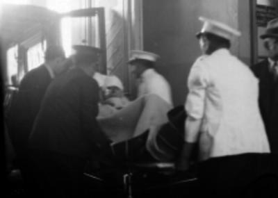 Policías trasladando a un detenido herido hacia un hospital, en una ambulancia