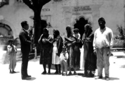 Hombre conversando con varias mujeres en la calle, probablemente durante una investigación