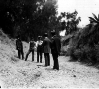 Agentes del Ministerio Público conversando con unos hombres durante averiguaciones en un camino rural