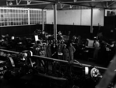 Obreros y obreras rodean a visitante distinguido en una fábrica, retrato de grupo