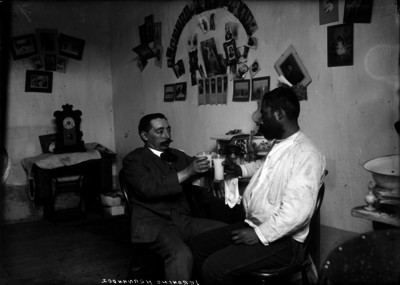 Jerónimo Hernández, periodista, brindando con un señor en una habitación