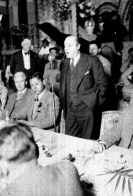 Periodista hablando ante otras personas durante un banquete