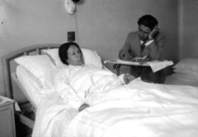 Miguel Gil entrevistando a una enferma, en un hospital