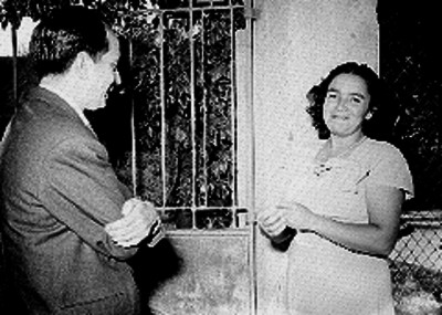 Periodista y mujer de clase media en la entrada de un jardín de una casa