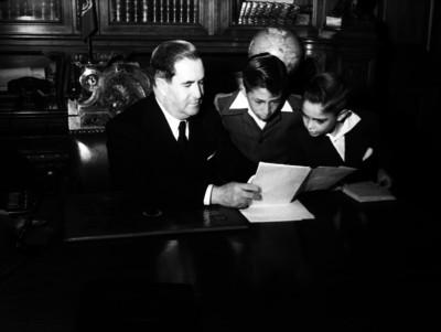 Manuel Ávila Camacho muestra libro a niños, en oficina de Palacio Nacional