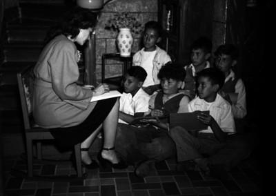 Maestra enseña a escribir a un grupo de niños