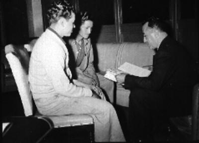 Manuel Espejel lee libro frente a dos personas