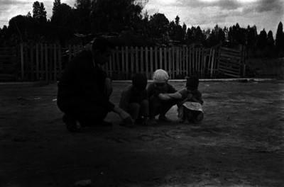 Hombre con niños, dibujan letras en la tierra