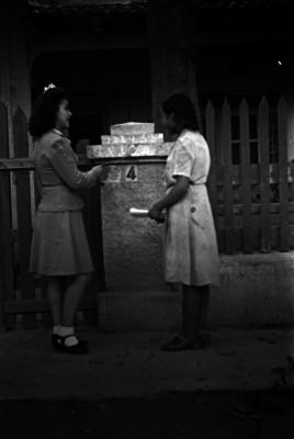 Alfabetizadora y mujer a las puertas de una casa habitación
