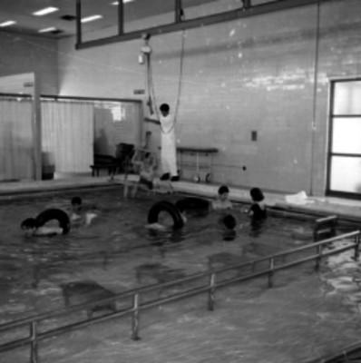 Piscina de hidroterapia con enfermeras, ayudante y pacientes