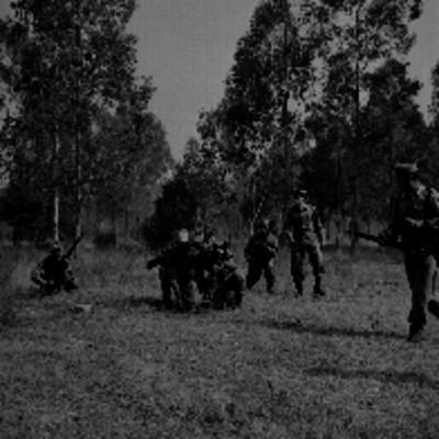 Soldados preparando el armamento bajo la suspensión del coronel Arciga de los Cobos durante una práctica militar